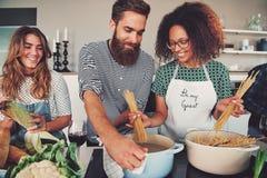 Tre vänner som lagar mat spagetti arkivfoton