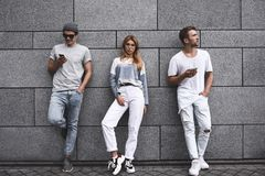 Tre vänner som lutar till en vägg och ignorerar sig royaltyfri bild