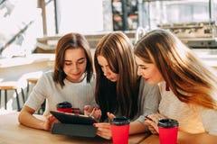 Tre vänner som shoppar på online-lagret royaltyfria bilder