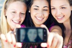 Tre vänner som tar foto med en smartphone Arkivbild