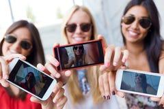 Tre vänner som tar foto med en smartphone Arkivbilder
