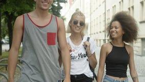 Tre vänner som till varandra talar som dem som tillsammans går i en stad Arkivbild