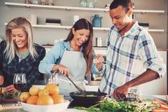 Tre vänner som tillsammans steker mat i panna Royaltyfri Bild