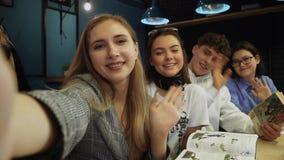 Tre vänner tar en selfie och en våg på den kameran med hälsningar som sitter i ett kaffehus med böcker och anmärkningar stock video