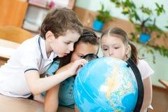 Tre vänner undersöker ett skolajordklot arkivfoton
