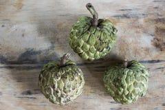 Tre vaniljsåsäpplen på ett träbräde arkivbilder