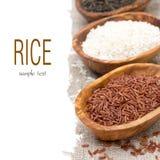 Tre varietà di riso crudo in ciotola di legno, fuoco selettivo Fotografie Stock