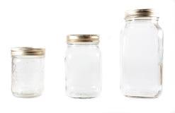 Tre vasi di muratore di vetro su una priorità bassa isolata Immagine Stock