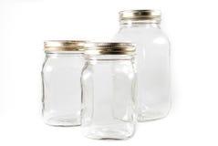 Tre vasi di muratore di vetro su una priorità bassa isolata Immagini Stock