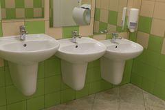 Tre vaskar av olika höjder i en offentlig toalett royaltyfri fotografi
