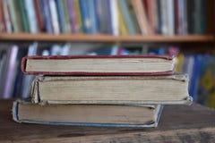 Tre vecchi libri in una biblioteca Fotografia Stock