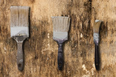 Tre vecchie spazzole su una superficie di vecchio e di sporco Immagine Stock Libera da Diritti