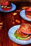 Tre vegetariska hamburgare i rosa bullar på blåa plattor fotografering för bildbyråer