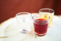 Tre vetri con differenti liquidi su un supporto di legno di un genere rotondo, di un colore liquido trasparente e giallo rosso Immagini Stock
