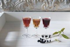 Tre vetri con liquore multicolore su un fondo d'annata bianco immagini stock