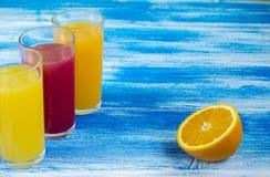 Tre vetri delle bibite sono su un fondo blu Fette di arancio Bevande di estate e stile di vita sano fotografie stock