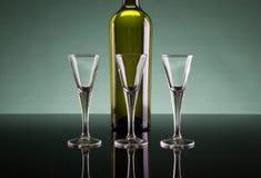Tre vetri di colpo e una bottiglia Fotografie Stock