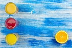 Tre vetri di succo fresco e dell'arancia affettata Bevande di estate e stile di vita sano Estate blu del fondo fotografie stock libere da diritti
