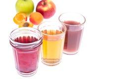 Tre vetri di vetro con i succhi delle bacche e della frutta fresca immagini stock libere da diritti