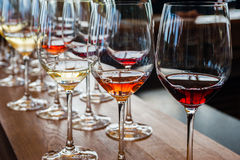 Tre vetri di vino con i campioni sul contatore di legno Immagine Stock