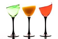 Tre vetri di vino con i liquidi colorati su un fondo bianco Fotografia Stock Libera da Diritti