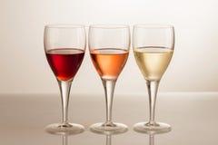 Tre vetri di vino su fondo bianco Immagini Stock