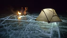 Tre viaggiatori da fuoco radrizzano su ghiaccio alla notte Campeggio su ghiaccio La tenda sta accanto a fuoco Lago Baikal Vicino  video d archivio