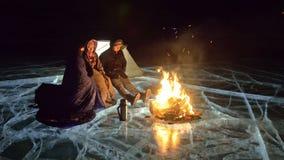Tre viaggiatori da fuoco radrizzano su ghiaccio alla notte Campeggio su ghiaccio La tenda sta accanto a fuoco Lago Baikal Vicino  stock footage