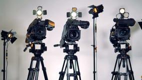 Tre videocamere professionali con i diffusori istantanei sopra stock footage