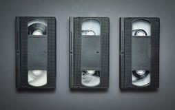 Tre videokassetter på en grå bakgrund Retro teknologi från 80-tal Arkivbilder