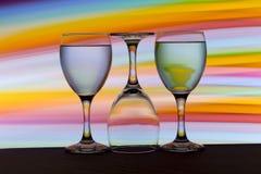 Tre vinexponeringsglas i rad med en regnbåge av färg bak dem royaltyfri foto