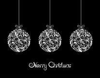 Tre vita julbollar på svart bakgrund.