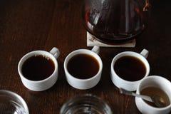 Tre vita koppar med kaffe på avsmakning Arkivbild