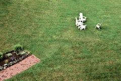 Tre vita och stolar för en solbrända gräsmatta på en stor gräsmatta royaltyfri foto