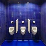 Tre vita pissoar i offentlig toalett för män mot den blåa väggen Arkivfoto