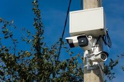 Tre vita utomhus- CCTV-kameror på den konkreta pelaren på set Arkivfoton