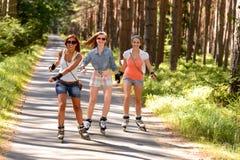 Tre vänner på i-linje åker skridskor utomhus- Arkivfoto