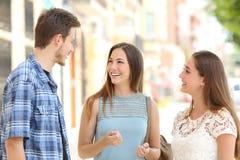 Tre vänner som talar ta en konversation på gatan Royaltyfria Bilder