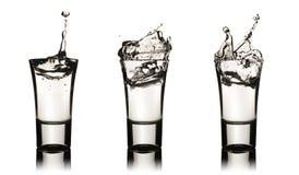 Tre vodkaexponeringsglas med färgstänk Arkivbild