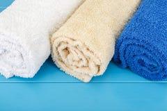 Tre vridna handdukar på en blå träbakgrund Royaltyfria Bilder