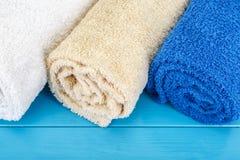 Tre vridna handdukar på en blå träbakgrund Royaltyfri Foto