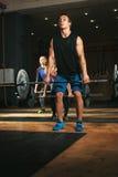 Tre vuxna människor som övar med skivstånger i idrottshall Royaltyfri Bild
