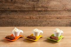 Tre whipcreamespresso som tjänas som med läckra chokladsconeser fotografering för bildbyråer
