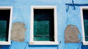 Tre Windows in Burano sulla parete del blu di decadimento fotografia stock libera da diritti