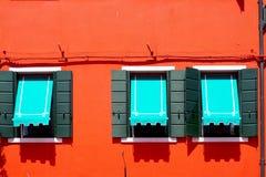 Tre Windows con il baldacchino blu in Burano sulla parete arancio rossa Fotografia Stock