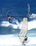 Tre windsurfers nelle onde Immagini Stock