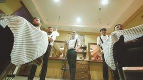 Tre yrkesmässig barberare eller frisör som tillfredsställs med resultatet av deras arbetsvridningstolar med kunder med arkivfilmer