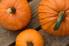 Tre zucche arancio luminose su legno Fotografia Stock