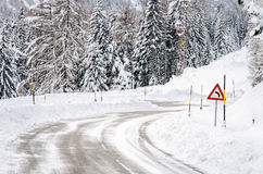 Treacherous Driving Conditions in the Mountains in Winter. Winding Mountain Road Covered with Snow with a Warning Road Sign before a Dangerous Sharp Bend Royalty Free Stock Photo