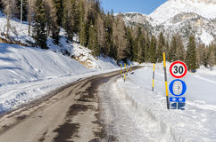 Treacherous Frozen Mountain Road. Treacherous Mountain Road and Warning Signs in the Italian Alps Stock Images
